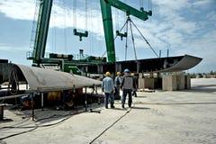 工作在大起重机之间的一个造船厂的有些工作者兆游艇的建筑的 库存照片