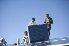 工作在太阳电池板的工作者反对蓝天 免版税库存图片
