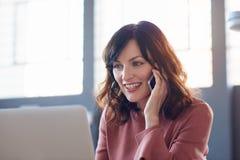 工作在她的书桌的微笑的女实业家在一个现代办公室 免版税图库摄影