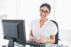 工作在她的书桌的快乐的女实业家看照相机 免版税库存图片
