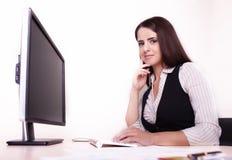 工作在她的书桌的快乐的女实业家看照相机  免版税库存照片