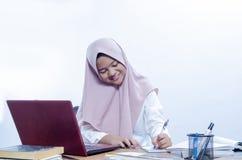 工作在她的办公室的微笑确信的年轻女人 库存照片