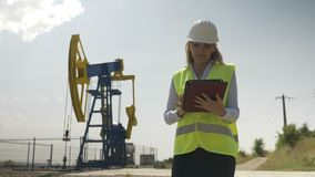 工作在她的在她的工作满意的油田产业的数字式片剂的美丽的工程学妇女评估者- 股票视频