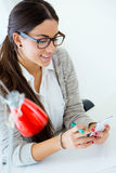 工作在她的有手机的办公室的年轻女实业家 免版税库存照片