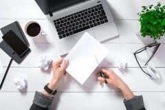 工作在她的有文件和膝上型计算机的办公桌的大角度观点的一个少妇 免版税库存照片