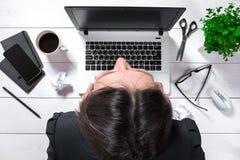 工作在她的有文件和膝上型计算机的办公桌的大角度观点的一个年轻浅黑肤色的男人 免版税库存图片