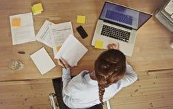 工作在她的有文件和膝上型计算机的办公桌的女实业家 免版税库存照片