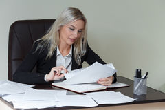 工作在她的有文件的办公桌的美丽的微笑的女商人 库存图片