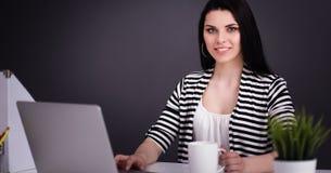 工作在她的有膝上型计算机的书桌的美丽的女商人 库存图片