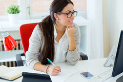 工作在她的有膝上型计算机的办公室的年轻女实业家 免版税库存照片