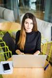 工作在她的有膝上型计算机的办公桌的大角度观点的一个年轻浅黑肤色的男人 女实业家重点笔记本办公室工作 免版税库存图片