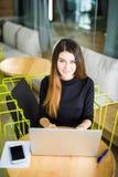 工作在她的有膝上型计算机的办公桌的大角度观点的一个年轻浅黑肤色的男人 女实业家重点笔记本办公室工作 免版税图库摄影