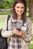 工作在她的未来派智能手机的愉快的少妇 图库摄影