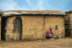 从工作在她的村庄h前面的马塞人部落的非洲妇女 免版税库存图片