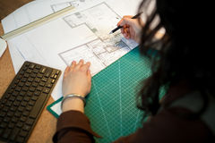 工作在她的桌上的图纸的建筑师 图库摄影
