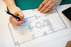 工作在她的桌上的图纸的建筑师 免版税图库摄影