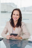 工作在她的片剂个人计算机的微笑的女实业家 免版税图库摄影