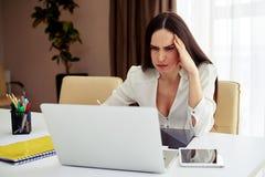 工作在她的笔记本的浅黑肤色的男人在一个现代办公室 免版税库存图片