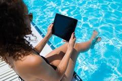 工作在她的触摸板的少妇,当晒日光浴在游泳池附近在旅馆里时 免版税库存图片