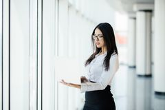 工作在她的豪华办公室的年轻女商人拿着站立反对全景窗口的膝上型计算机有在企业二的一个看法 库存照片