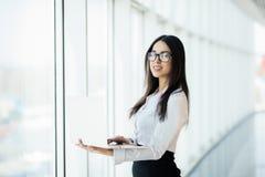 工作在她的豪华办公室的年轻女商人拿着站立反对全景窗口的膝上型计算机有在企业二的一个看法 库存图片