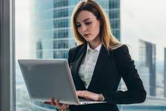工作在她的豪华办公室的年轻女性律师拿着站立反对全景窗口的膝上型计算机有看法  图库摄影