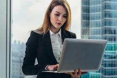 工作在她的豪华办公室的年轻女性律师拿着站立反对全景窗口的膝上型计算机有看法  库存图片