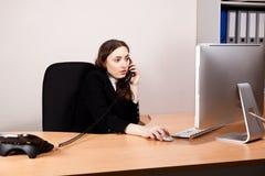 工作在她计算机和叫上的女商人 免版税库存图片