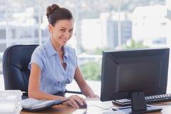 工作在她计算机和微笑上的女实业家 库存图片