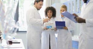工作在实验室的小组科学家谈论化学制品在烧瓶和试管分析研究实验 影视素材