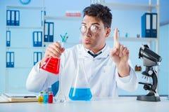 工作在实验室的滑稽的疯狂的化学家 免版税库存图片