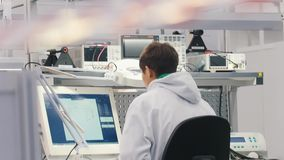工作在实验室的电子工程师 坐在桌上和研究计算机的工程师,看 股票录像
