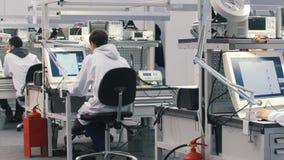 工作在实验室的电子工程师 坐在桌上和研究计算机的工程师 新的专业人员 股票视频