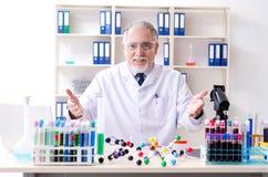 工作在实验室里的老男性化学家 免版税图库摄影