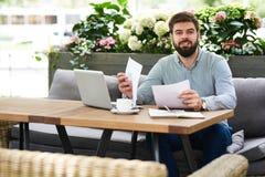 工作在室外咖啡馆的微笑的企业家 库存图片