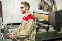 工作在家具工厂的年轻人 免版税库存照片