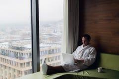 工作在家或在旅行的买卖人 英俊的年轻商人侧视图画象坐床和使用 免版税库存照片