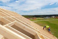 工作在屋顶的建筑队反对蓝天 免版税库存图片