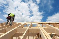 工作在屋顶的建筑队反对蓝天 免版税库存照片