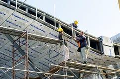 工作在屋顶设施的外籍工人 库存图片