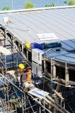 工作在屋顶设施的外籍工人 图库摄影