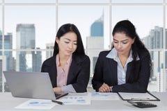 工作在工作场所的两名女实业家 免版税库存照片
