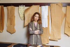 工作在工作室,纸在背景的布料paterns的成人时尚编辑 免版税库存图片