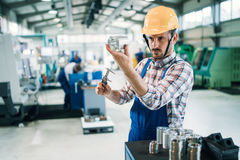 工作在工厂的现代工业机器操作员 免版税库存图片