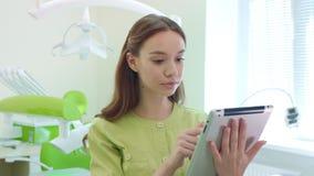 工作在平板电脑的医科学生在牙齿办公室 使用片剂的妇女医生