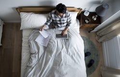 工作在床上的日本人 免版税库存照片