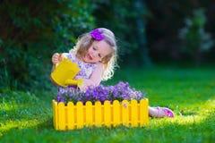 工作在庭院浇灌的花的小女孩 库存图片