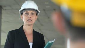 工作在建造场所的一名年轻建筑师妇女,谈话与她的同事 免版税图库摄影