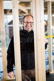 工作在建造场所的愉快的男性木匠 库存照片