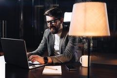 工作在当代笔记本的微笑的年轻有胡子的商人在顶楼办公室在晚上 免版税库存照片